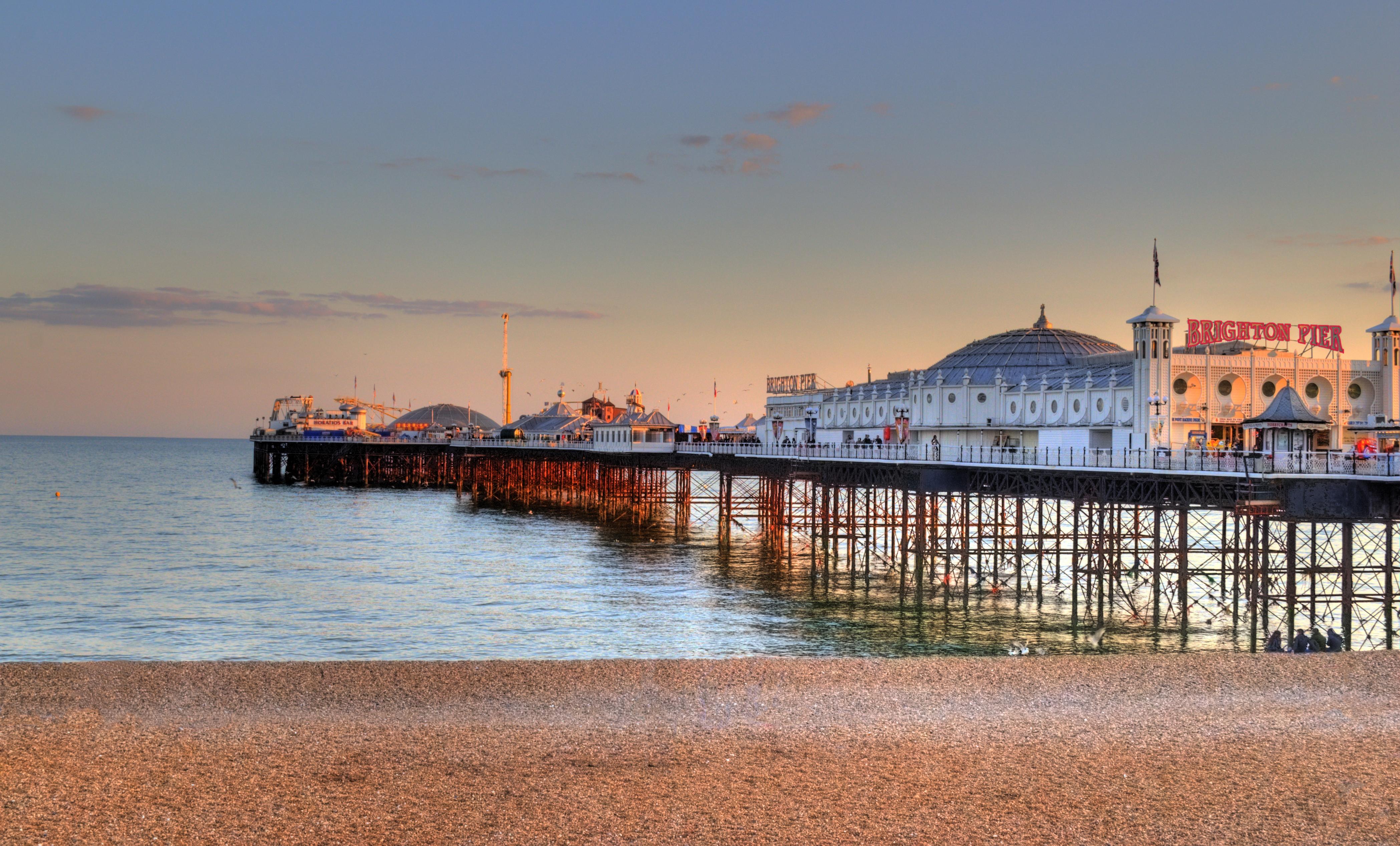Panorámica del muelle de Brighton, con la playa, el muelle y los pabellones recreativos de fondo