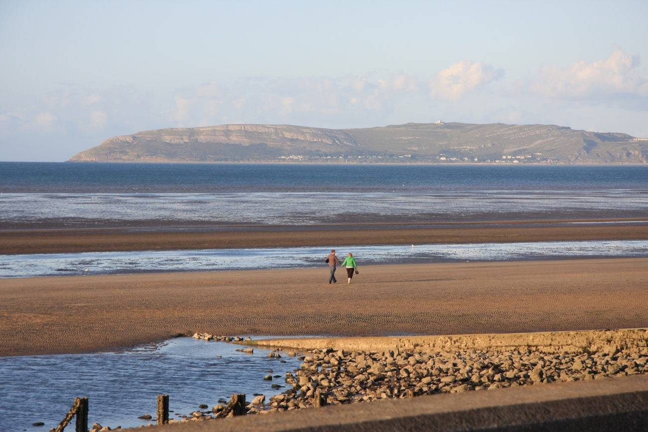 John Clark - A couple walking along Llanfairfechan beach