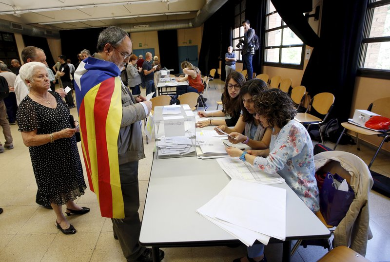 "A man, wearing a ""Estelada"" (Catalan separatist flag) casts his vote during municipal elections in Barcelona"