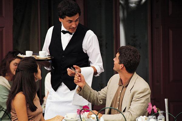 Un camarero atiende a unos clientes en un restaurante